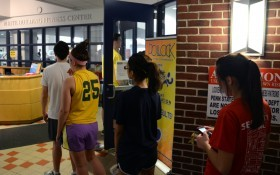 Students wait in line to use the fitness center at the White Building Monday evening.  Students have waited upwards of an hour at times. (Photo by: Michael Misciagno)