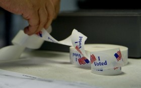 "A voter peels off an ""I Voted"" sticker a"