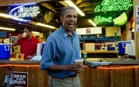 Barack Obama looks pumped as he gets some fresh food and cold beer from a bar.