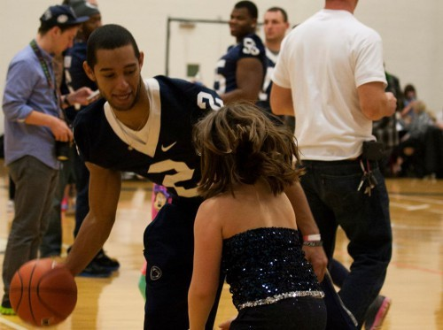 Penn State wide receiver Jake Kiley crosses over a THON child in a pickup game of basketball. Take it easy, there, will you? (Photo by: Bobby Chen)
